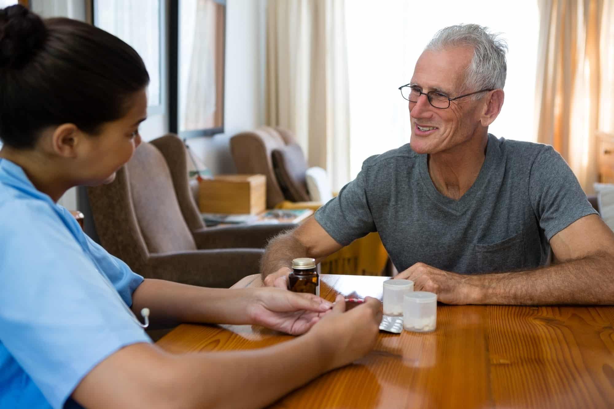 Senior man talking to female doctor in nursing home