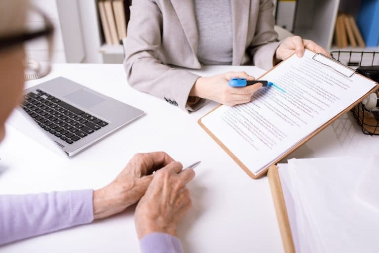 Hands of insurance agent underlining important phrase in document